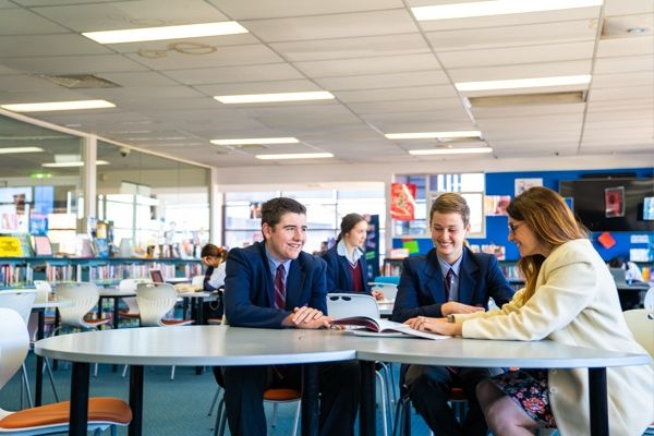 St Patrick's College Sutherland - teacher and students looking at a booklet